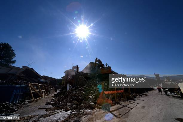 Picture taken on August 23, 2017 in Amatrice shows a machine on rubble, a year after a deadly earthquake left nearly 300 people dead and destroyed...