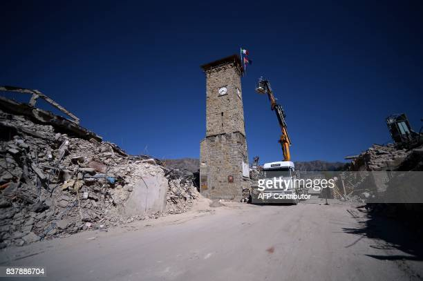 A picture taken on August 23 2017 shows a truck and an aerial bucket next to the remains of Amatrice a year after a deadly earthquake left nearly 300...