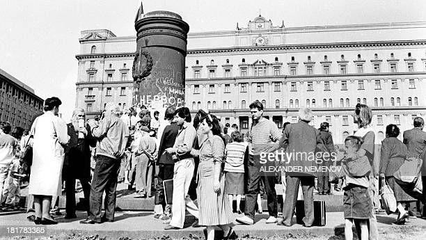 A picture taken on August 23 shows people gather in front of a KGB building with a ruined monument to its founder Felix Dzerzhinski in front of it in...