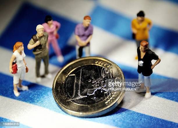 A picture taken on August 24 2012 in Lille shows an illustration made with figurines and a euro coin set on a Greek flag Greek Prime Minister Antonis...