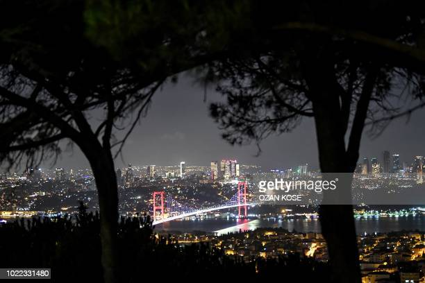 Picture taken on August 24, 2018 in Istanbul shows a night view of July 15 Martyrs' Bridge , known as the Bosphorus Bridge and the financial district...