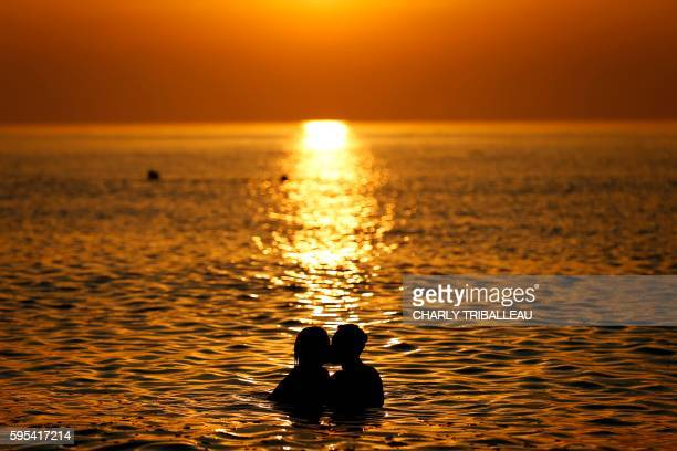 A picture taken on August 25 2016 shows a couple kissing as they swim in the sea at sunset in SaintMartinauxBuneaux northwestern France / AFP PHOTO /...
