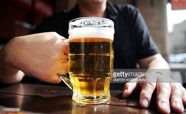 A picture taken on August 26 2011 shows a man holding a glass of beer in a Moscow's outdoor pub With a stroke of the presidential pen beer was...