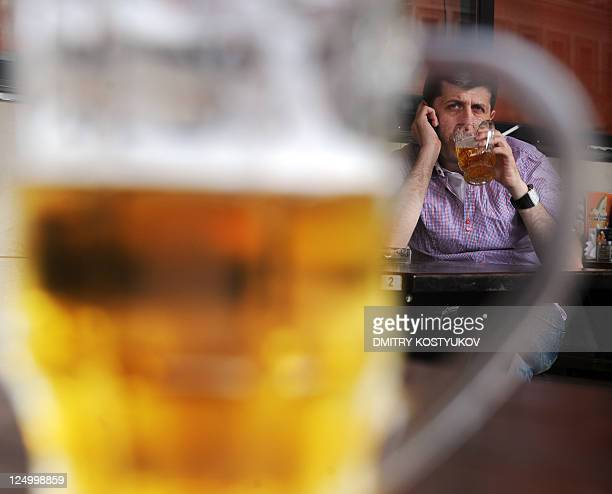 A picture taken on August 26 2011 shows a man sitting in behind a glass of beer in a Moscow's outdoor pub With a stroke of the presidential pen beer...