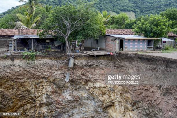 Picture taken on August 26, 2018 showing part of a sinkhole which first appeared in July after the collapse of the surface layer and grew bigger as...