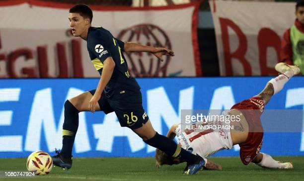 Picture taken on August 26 2018 shows Boca Juniors' defender Leonardo Balerdi controlling the ball past Huracan's midfielder Ivan Rossi during an...