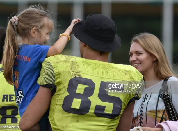 A picture taken on August 26 shows American Football player of Ukarnian team Kyiv Rebels speaking with relatives at the end of an American Football...