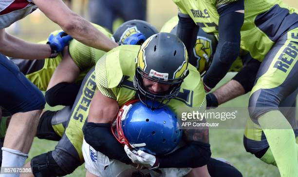 A picture taken on August 26 shows American Football players of Ukarnian team Kyiv Rebels wearing the green jersey fighting for the ball against the...
