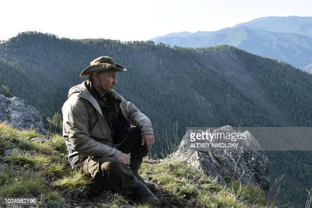 TOPSHOT A picture taken on August 26 shows Russian President Vladimir Putin sitting on a mountain ridge during a short vacation in the remote Tuva...