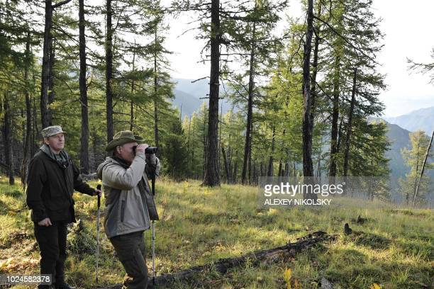A picture taken on August 26 shows Russian President Vladimir Putin looking through binoculars flanked by Director of the Federal Security Service...
