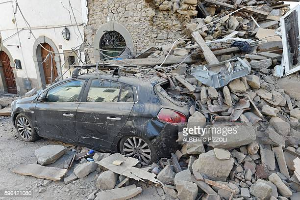 Picture taken on August 27, 2016 shows a damaged car in San Lorenzo, near the Italian village of Amatrice, three days after a 6.2-magnitude...