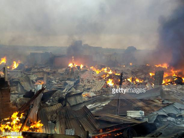 Picture taken on August 27, 2019 shows burning rubbles in the market of Bouake, central Ivory Coast, after a fire broke overnight.