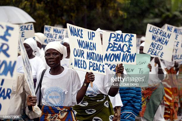 A picture taken on August 28 2003 shows Liberian women staging a protest march in front of the ECOMIL headquarters in Monrovia Liberian President...