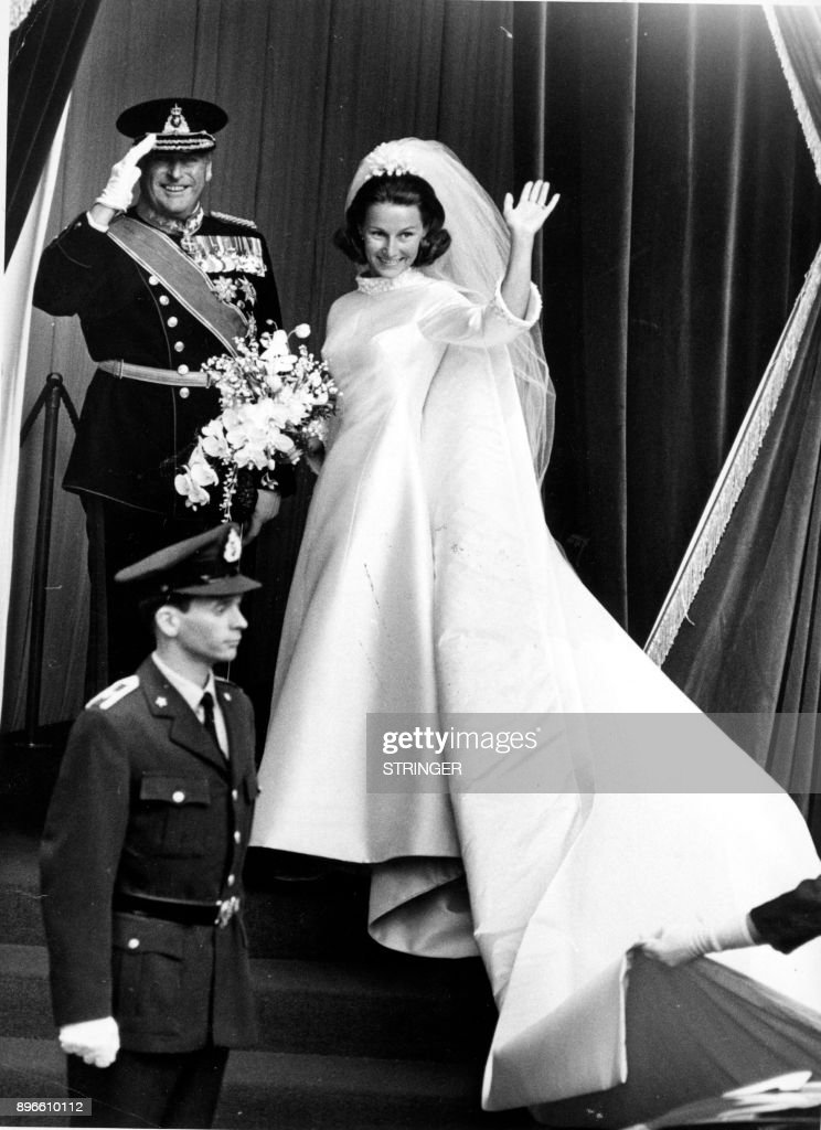 A picture taken on August 29, 1968 shows Norway's Crown Prince Harald and Sonja Haraldsen waving outside the Oslo Cathedral during their wedding. / AFP PHOTO / NTB scanpix / STRINGER / Norway OUT