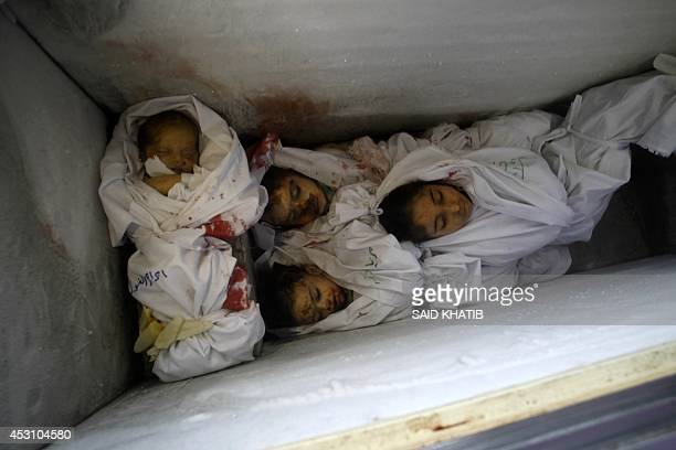 A picture taken on August 3 at the morgue of a hospital in Rafah in the southern Gaza Strip shows the bodies of a baby and three children lying in an...