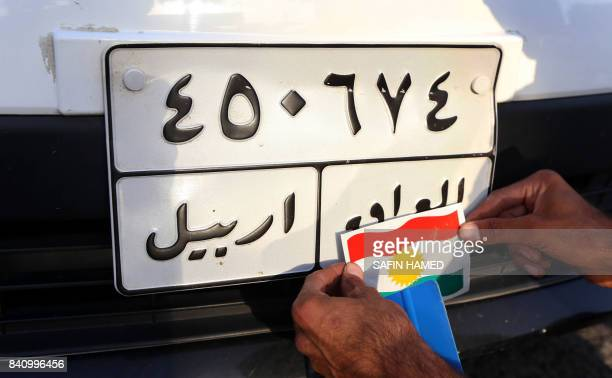 A picture taken on August 30 2017 in Arbil the capital of the autonomous Kurdish region of northern Iraq shows a man putting up a sticker of the...
