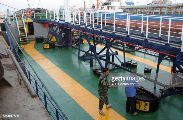 A picture taken on August 30 2017 shows Libyan security personnel aboard the deck of an oil tanker on tow in the port of the Libyan capital Tripoli...