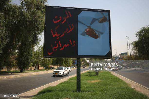 TOPSHOT A picture taken on August 30 2019 shows a billboard installed by a militant faction belonging to Iraq's Hashed alShaabi on a main road in...