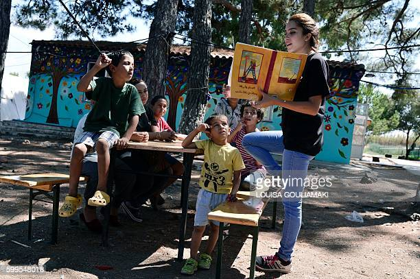 A picture taken on August 31 2016 shows children listening to a story read by a volunteer at the ' Village All together' or PIKPA village on the...