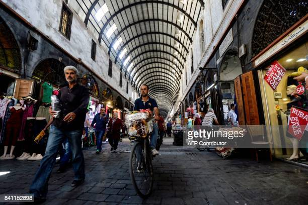 A picture taken on August 31 2017 shows a Syrian man riding a bicycle as others shop at the Medhat Pasha market in the old part of the capital...