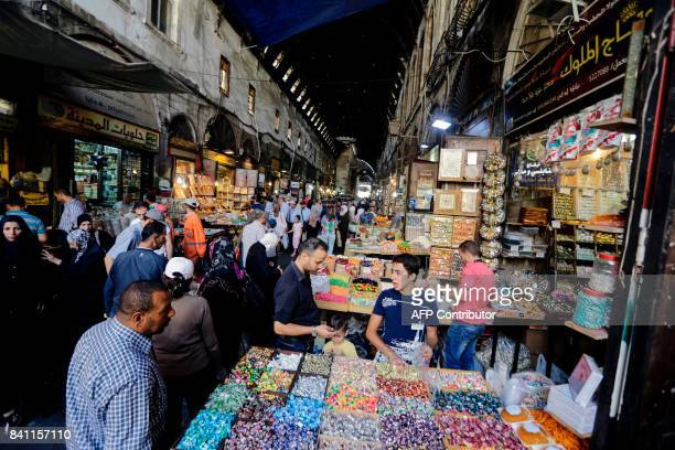 A picture taken on August 31 2017 shows Syrian shopping for sweets at alBazourieh popular market in the old part of the capital Damascus in...