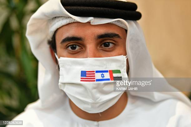 Picture taken on August 31 shows an Emirati man, wearing a protective mask with the flags of the US, Israel and the UAE, ahead of the arrival of the...