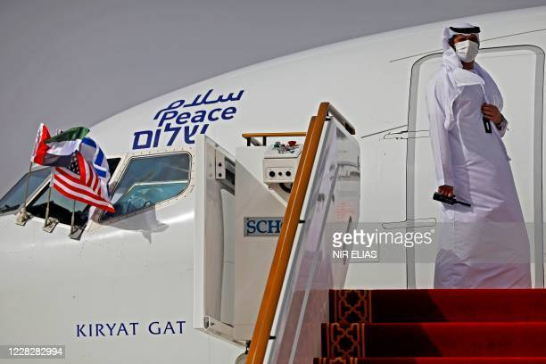 Picture taken on August 31 shows an Emirati official preparing to open the door of the El Al's airliner, which is carrying a US-Israeli delegation to...