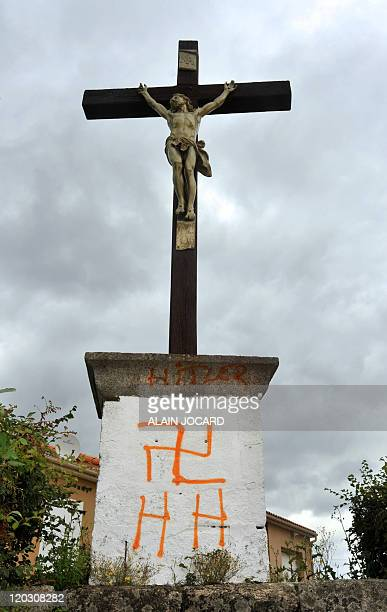 A picture taken on August 4 2011 in the French central town of Fomperron shows a swastika and nazi inscriptions under a large outdoor crucifix As the...