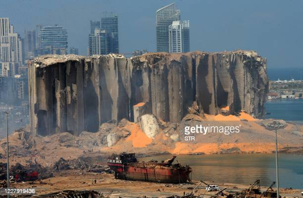 TOPSHOT A picture taken on August 5 2020 shows the damaged grain silo and a burnt boat at Beirut's harbour one day after a powerful twin explosion...