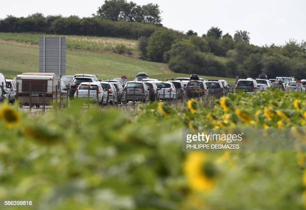 TOPSHOT A picture taken on August 6 2016 shows a field of sunflowers next to traffics jams between Vienne and Valence on the A7 motorway in Vienne...
