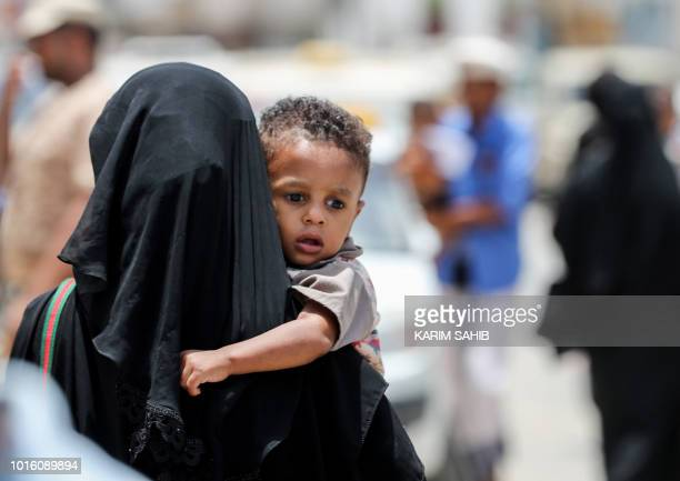 A picture taken on August 7 2018 during a trip in Yemen organised by the UAE's National Media Council shows a Yemeni woman carrying a child to a...