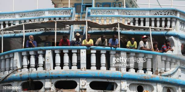 A picture taken on August 8 2018 during a trip in Yemen organised by the UAE's National Media Council shows Yemeni fishermen standing on a large...