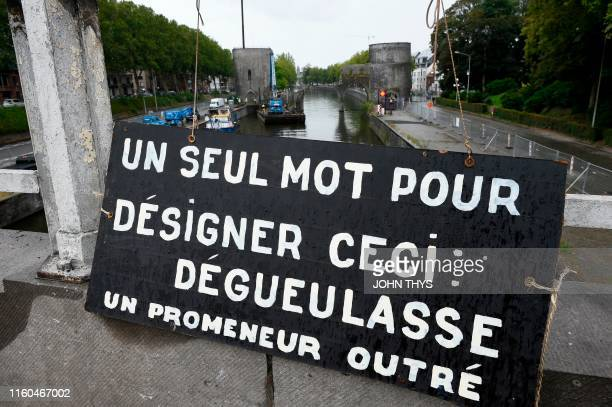 "Picture taken on August 9, 2019 shows a placard reading "" Only one word to describe this : disgusting. An outraged passerby."" near the ""Pont des..."