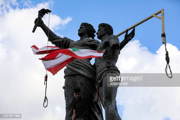 Picture taken on August 9, 2020 shows gallows hanging above a Lebanese flag on central Beirut's landmark Martyrs Statue, as protesters returned to...
