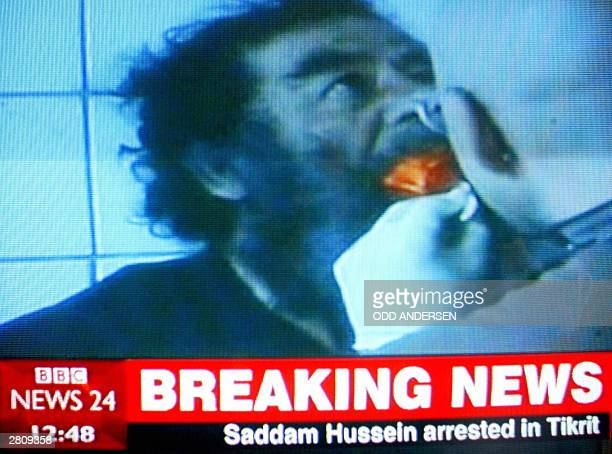 A picture taken on BBC News 24 showings an image of the coalition video of Saddam Hussein getting a medical check up after his capture broadcasted 14...