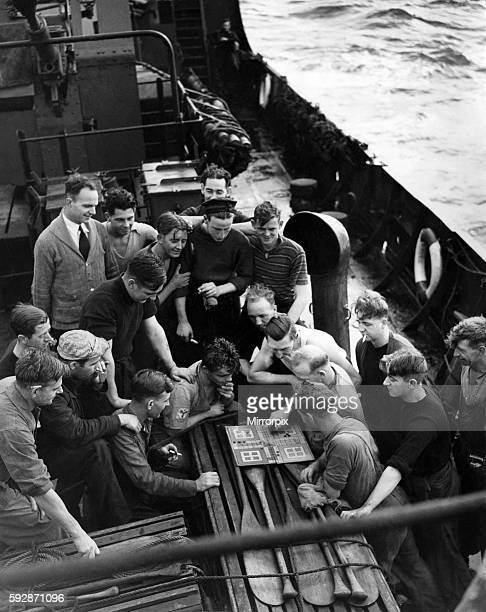Picture taken on board one of HMS Escort Vessels during a West Coast of England Convoy. Some of the crew are watching an exciting game of Ludo on the...