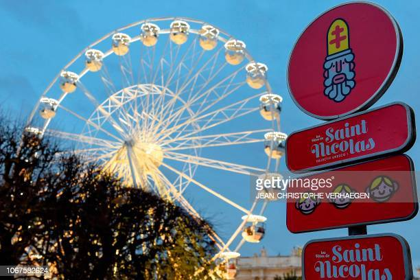 Picture taken on December 1, 2018 shows street signs depicting Saint Nicholas's characters with a Ferris wheel in background during the festivities...