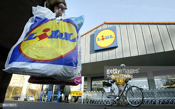 FILES Picture taken on December 10 2004 shows a Lidl customer carrying a shopping bag in front of a supermarket of the German retail chain in...