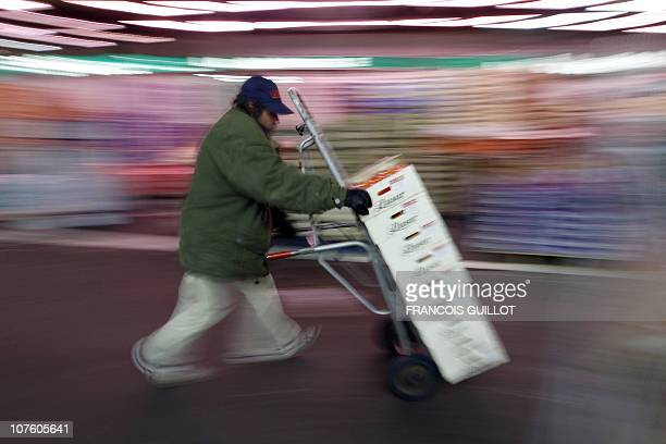 A picture taken on December 10 2010 shows a man pushing a char carrying fruits in the fruit and vegetable pavilion at Rungis international food...