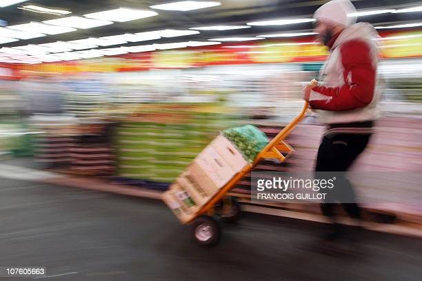 A picture taken on December 10 2010 shows a man pushing a char carrying vegetables in the fruit and vegetable pavilion at Rungis international food...
