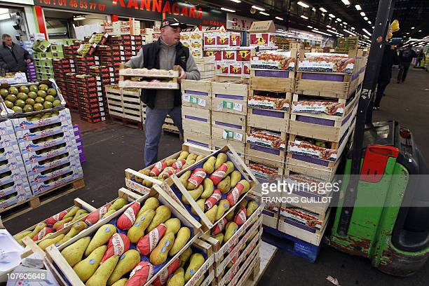 A picture taken on December 10 2010 shows a man working on a char carrying fruits in the fruit and vegetable pavilion at Rungis international food...