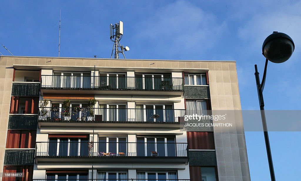A picture taken on December 10, 2012 in Paris shows a mobile phone mast on the rooftop of a residential building.