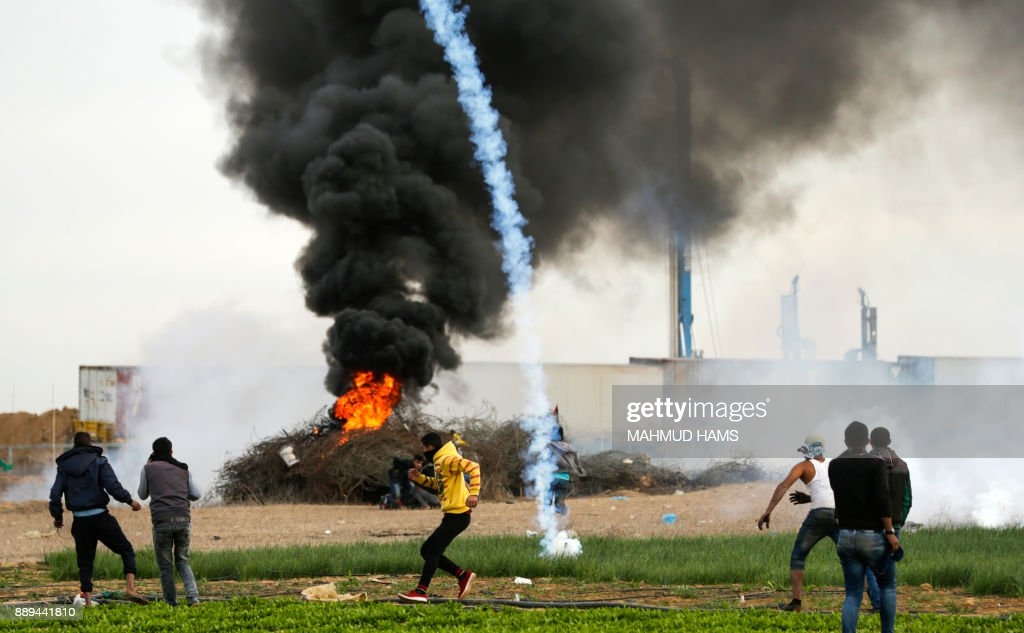 TOPSHOT - A picture taken on December 10, 2017 shows a tear gas cannister falling amdist Palestinian protesters during clashes with Israeli forces near the Israel-Gaza border east of the southern Gaza strip city of Khan Yunis, with Israeli heavy machinery seen in the background on the other side of the border after a tunnel was discovered in the area. New protests flared in the Middle East and elsewhere over US President Donald Trump's December 6 declaration of Jerusalem as Israel's capital, a move that has drawn global condemnation and sparked days of unrest in the Palestinian territories. /