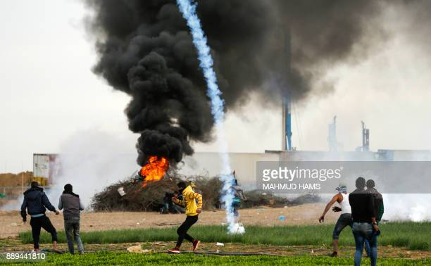 TOPSHOT A picture taken on December 10 2017 shows a tear gas cannister falling amdist Palestinian protesters during clashes with Israeli forces near...