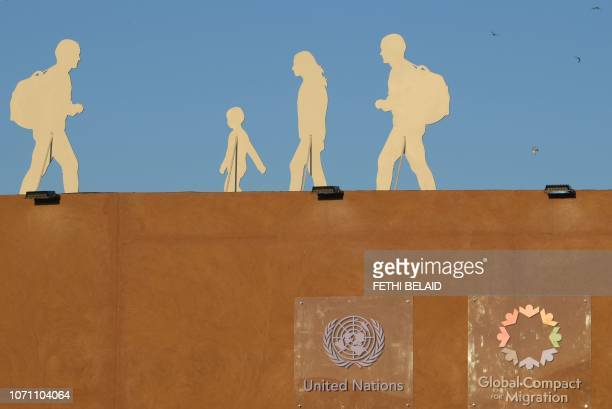 TOPSHOT A picture taken on December 10 2018 shows silhouettes of migrants installed at the grounds of the International conference on Global Compact...