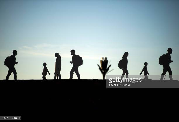 TOPSHOT A picture taken on December 10 2018 shows silhouettes of migrants part of an art installation at the grounds of the International conference...