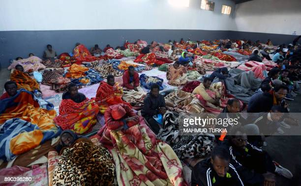 TOPSHOT A picture taken on December 11 2017 shows African migrants sitting in a shelter at the Tariq AlMatar migrant detention centre on the...