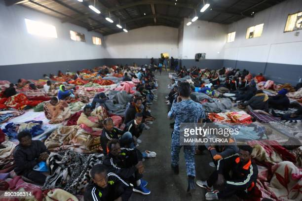 A picture taken on December 11 2017 shows African migrants sitting in a shelter at the Tariq AlMatar migrant detention centre on the outskirts of the...