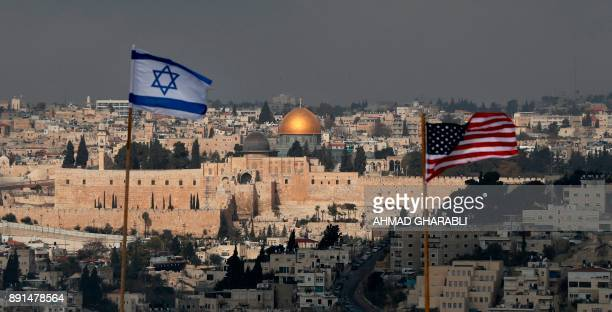 A picture taken on December 13 shows the Israeli and US flags placed on the roof of an Israeli settlement building in East Jerusalem and Jerusalem's...