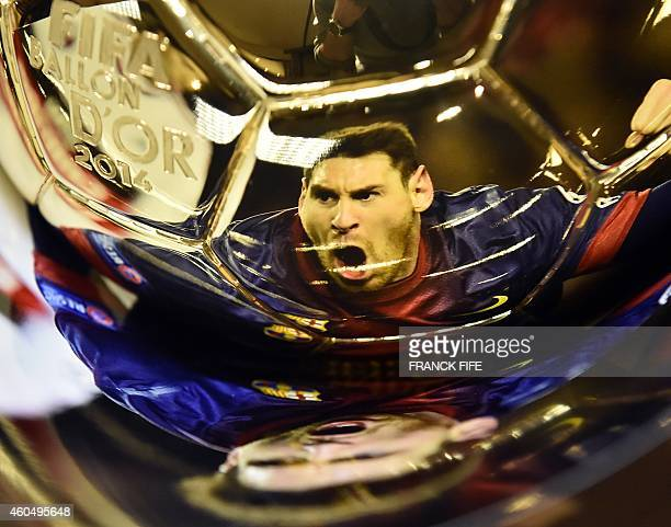 A picture taken on December 15 2014 shows a picture of Argentina's Lionel Messi reflecting itself in the 2014 Ballon d'Or trophy at the Mellerio...